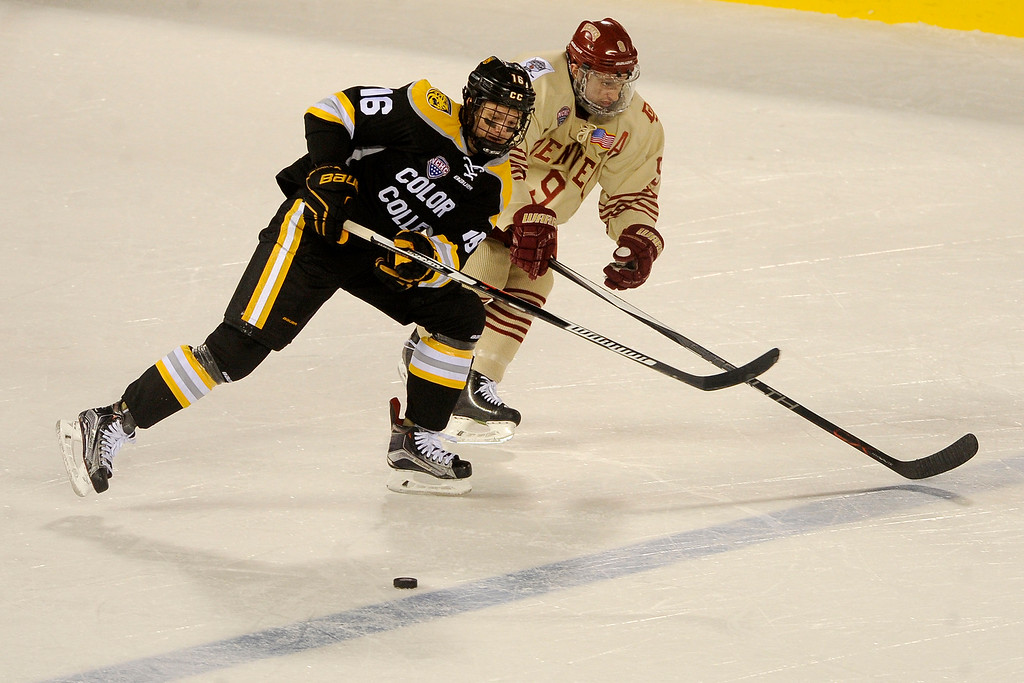 . Teemu Kivihalme (16) of Colorado College shrugs Gabe Levin (9) of the University of Denver off as he carries the puck into the zone during the second period at Coors Field in Denver, Colorado on February 20, 2016. (Photo by Seth McConnell/The Denver Post)