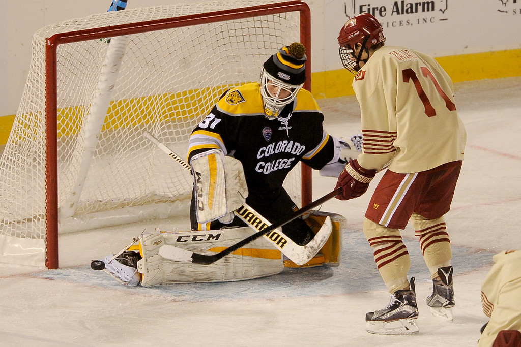 . Colorado College goalie Jacob Nehama (31) makes a kick save on a soft shot by Nolan Zajac (11) of the University of Denver during the second period at Coors Field in Denver, Colorado on February 20, 2016. (Photo by Seth McConnell/The Denver Post)