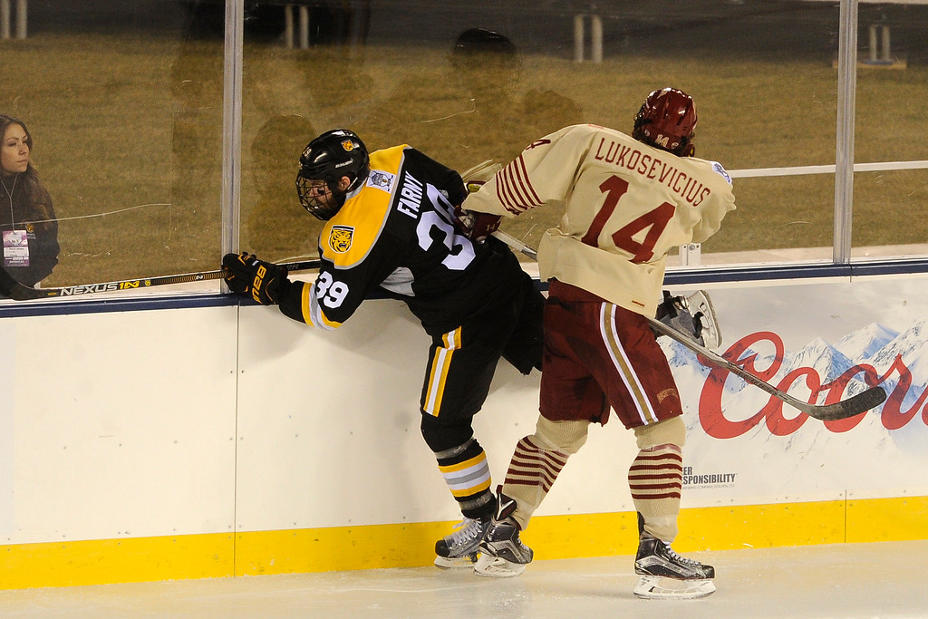 . Jarid Lukosevicius (14) of the University of Denver checks Andrew Farny (39) of Colorado College into the boards during the second period at Coors Field in Denver, Colorado on February 20, 2016. (Photo by Seth McConnell/The Denver Post)