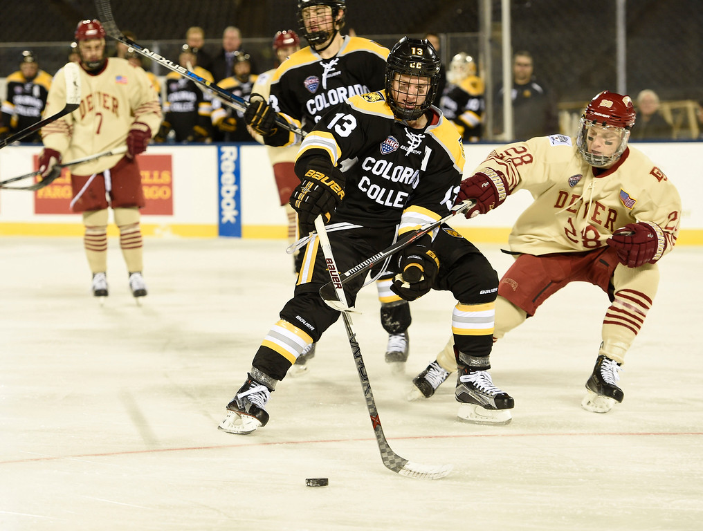 . Colorado College Tigers forward Cody Bradley (13) tries to control the puck as Denver Pioneers defenseman Adam Plant (28) comes in on defense in the second period during the Battle On Blake February 20, 2016 at Coors Field.  (Photo By John Leyba/The Denver Post)