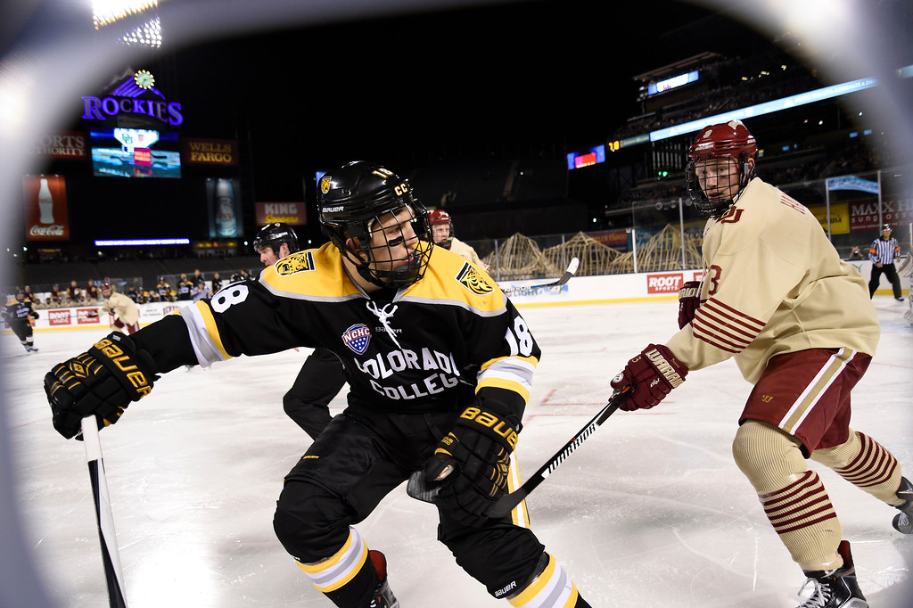 . Colorado College Tigers forward Hunter Fejes (18) and Denver Pioneers defenseman Tariq Hammond (3) look for the puck off a face-off in the second period during the Battle On Blake February 20, 2016 at Coors Field.  (Photo By John Leyba/The Denver Post)
