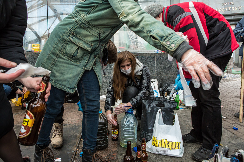 Description of  Women prepare Molotov cocktails for anti-government protesters near Independence Square on February 20, 2014 in Kiev, Ukraine. Dozens of protesters were reportedly been killed after violence flared again between police and anti-government protesters, who are calling to oust President Viktor Yanukovych over corruption and an abandoned trade agreement with the European Union.  (Photo by Brendan Hoffman/Getty Images)