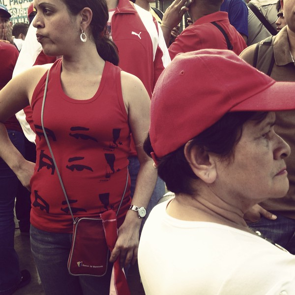 Description of  A woman wears a T-shirt with an image depicting the eyes of late Venezuelan former President Hugo Chavez during a Venezuelan President Nicolas Maduro rally in Caracas on January 23, 2014. A year after the death of President Hugo Chavez, the image that depicts his eyes are seen everywhere, from giant billboards and buildings to t-shirts and notebooks. This photo was taken with a mobile phone. LEO RAMIREZ/AFP/Getty Images