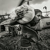 Local people helping unload a helicopter, the first aid to reach the remote community after Typhoon Haiyan. <br /> Mahagnau village, Leyte, Philippines, November 20, 2013.<br /> © Sean Sutton / MAG / Panos Pictures