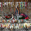 Prayer candles or votives sit in front of statues of Juan Diego who looks longingly at a statue of Our Lady of Guadalupe or the Virgin Mary. This is a spot where visitors can sit and pray and leave candles decorated with images of Saint Jude and the Virgin de Guadalupe. Also people who have prayed at this spot have left rosary beads hanging above. This spot is dedicated to the Virgin Mary and is located outside at El Santuario de Chimayó. (Photo by Hélène Casanova)