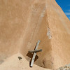 A hand made wooden cross left by an Easter Week pilgrim leans on an outside adobe walls of El Santuario de Chimayó. (Photo by Hélène Casanova)