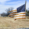 Worn American Flag stuck in a fence photographed in front of an old homestead farm in the surrounding area of Chimayo. (Photo by Hélène Casanova)
