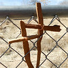 Hand made wooden crosses carried and left by pilgrims tucked into a fence by the side of the road in route to Chimayo. (Photo by Hélène Casanova)