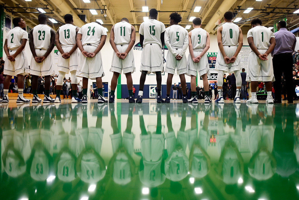 . The Overland players stand for the national anthem during the first half of play. The Overland Trailblazers hosted the Eaglecrest Raptors on Friday, January 8, 2016. (Photo by AAron Ontiveroz/The Denver Post)