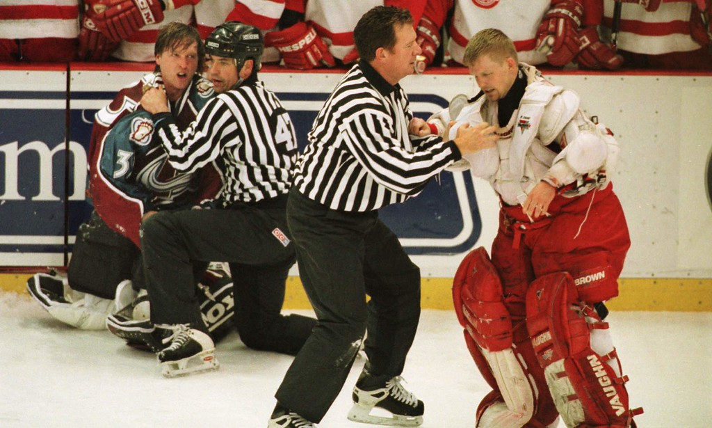 . [AVALANCHE RED WINGS  ]Linesmen Dan Schachte (47) and Dan McCourt separate Colorado Avalanche goalie Patrick Roy, left, and Detroit Red Wings goalie Chris Osgood after their mid-ice fight in the third period at Joe Louis Arena in Detroit, Wednesday, April 1, 1998. The Red Wings defeated the Avalanche, 2-0. (AP Photo/Carlos Osorio)