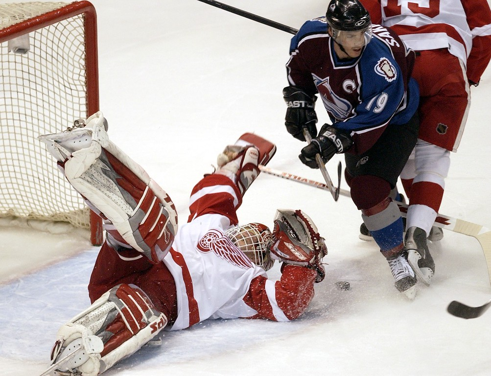 . Colorado Avalanche against the Detroit Red Wings in game 5 of the Western Conference Finals at Joe Louis Arena in Detroit. Wings goalie Dominik Hasek does his patented \'flop\' as he throws himself across the crease in second period action to stop the puck seen in the snow at the feet of Av captain Joe Sakic. (Photo by HYOUNG CHANG/ The Denver Post)