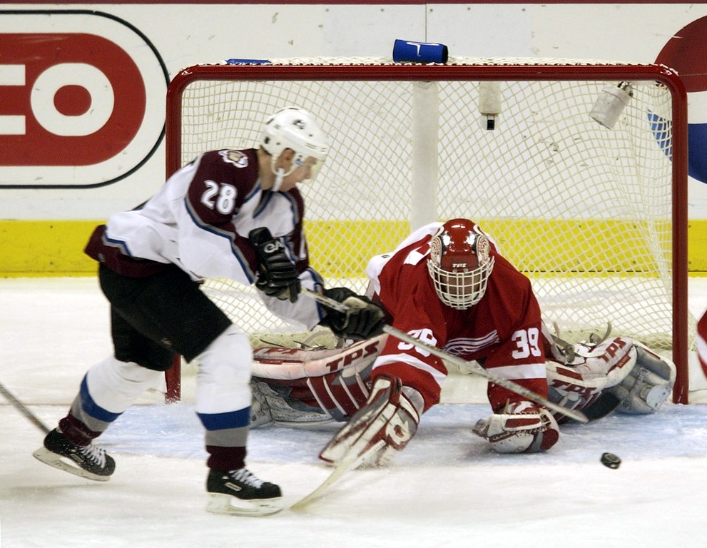 . CO Avalanche   Steven  Reinprecht takes a shot at the  Red Wings goalie Dominik Hasek  and scores in the frist period in Game 4 of the Western Conference playoffs.  5/24/02 Denver Post Photo Hyoung Chang.