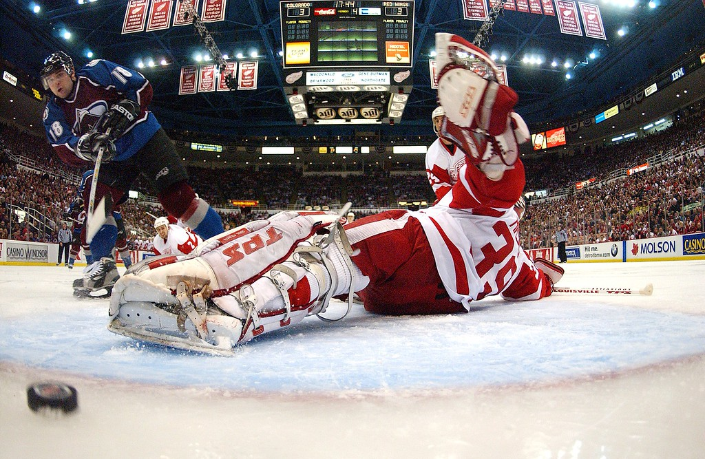 . DETROIT - MAY 20:   Chris Drury #18 of the Colorado Avalanche dekes and puts a shot into the net past goaltender Dominik Hasek #39 in the first overtime period of game two of the Western Conference Finals during the NHL Stanley Cup Playoffs at the Joe Louis Arena in Detroit, Michigan on May 20, 2002.The Avalanche won 4-3.  (Photo by Dave Sandford/Getty Images/NHLI)