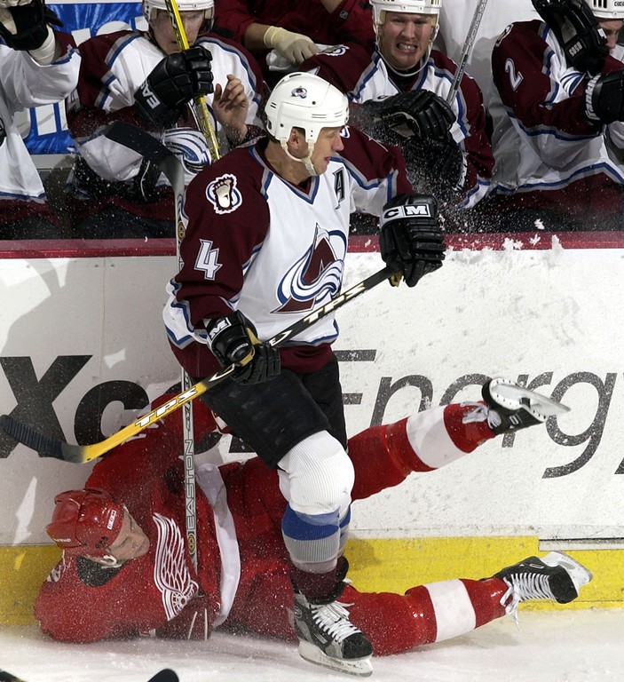 . Colorado Avalanche Rob Blake #4 pounds Detroit Red Wings Boyd Devereaux #21 up aginst the borads and ice during the third period at Pepsi Center February 8, 2003 as the Avalanche defeat the Red Wings 5-3.   Photo by John Leyba/ The Denver Post