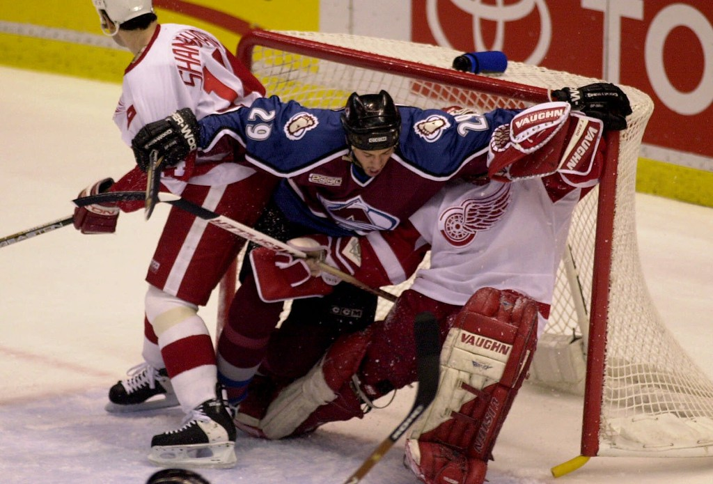 . Colorado Avalanche defenseman Eric Messier (29) collides into Detroit Red Wings goalie Chris Osgood, and winger Brendan Shanahan during the first period in their playoff game in Detroit, Monday, May 1, 2000. (AP Photo/Paul Sancya)