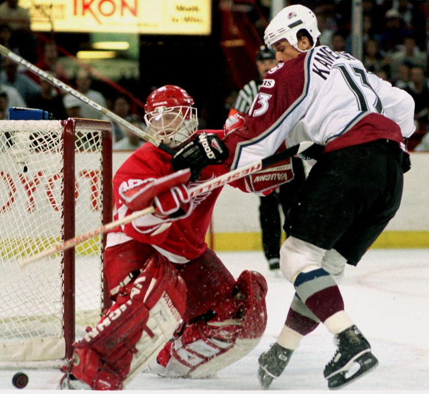 . Detroit Red Wings goalie Chris Osgood, left, gets tangled up with Colorado Avalanche left winger Valeri Kamensky as they battle for the puck in the first period of game five of the second-round playoff series in Denver\'s McNichols Sports Arena Sunday, May 16, 1999. (AP Photo/David Zalubowski)