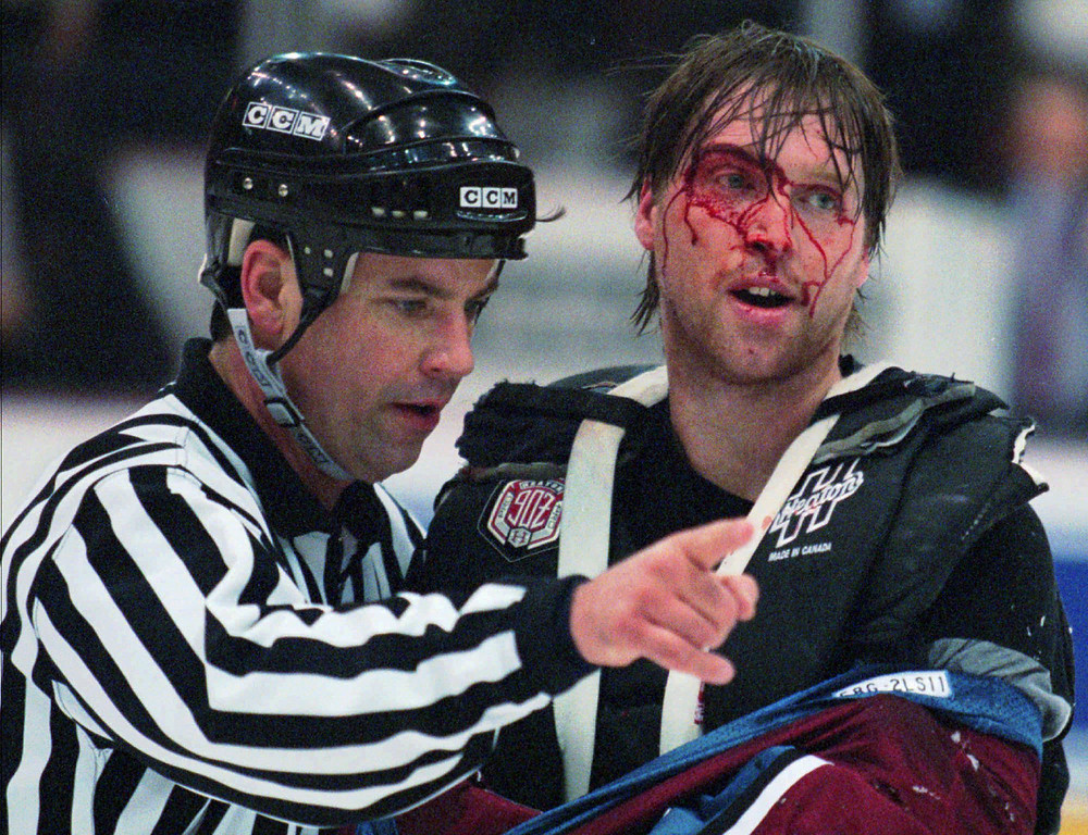 . Linesman Dan Schachte leads a bleeding Colorado Avalanche goaltender Patrick Roy to his bench after Roy was involved in a first period brawl with Detroit Red Wings\' goaltender Mike Vernon in Detroit on Wednesday, March 26, 1997.(AP Photo/Tom Pidgeon)