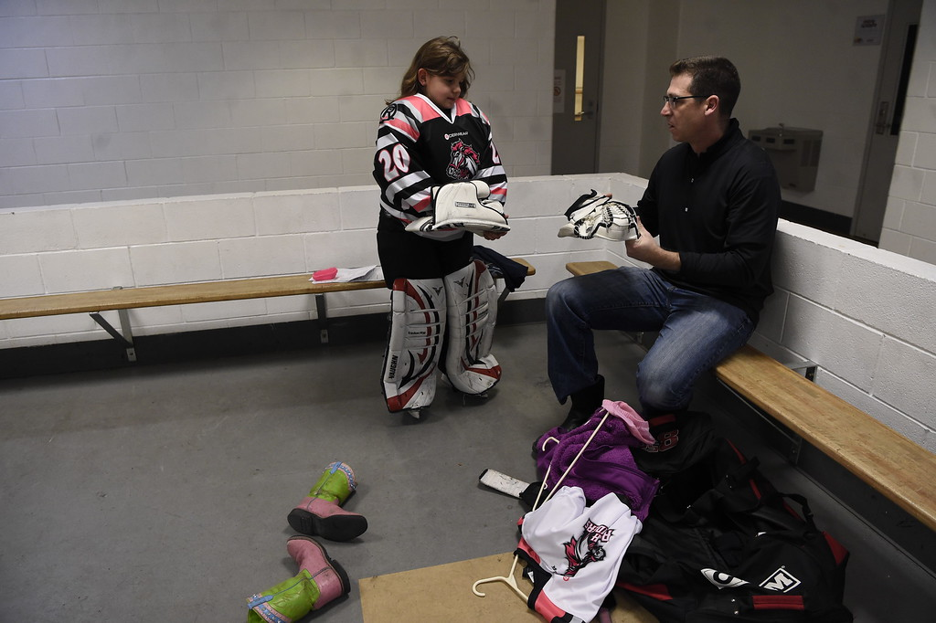 . Girls playing in hockey has become quite popular as Vera Poirier of the Lady Rough Riders gets a little help from dad Greg Poirier before their game February 21, 2016 at the Ice Center at the Promenade. The growth of hockey in Colorado has gone up  in the last 20 years since The Avalanche came to town. (Photo By John Leyba/The Denver Post)