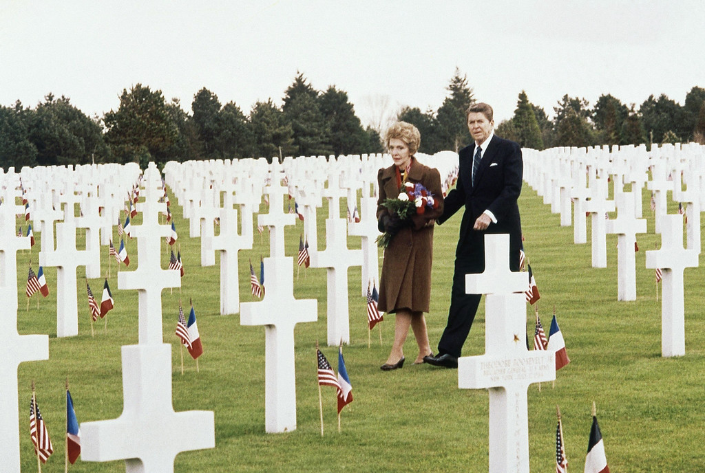 . President Ronald Reagan and his wife Nancy walk through the graves at Normandy American Cemetery in Omaha Beach, France on Wednesday, June 6, 1984 as they arrived to attend the 40th anniversary of the allied invasion 1944. In foreground is the grave of Theodore Roosevelt Jr., who died in the Normandy 1944. (AP Photo/Edmonds)
