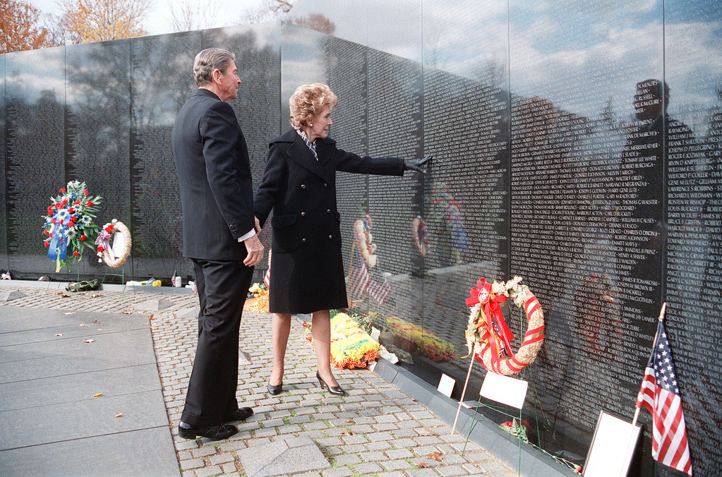 ". US President Ronald Reagan watches as First Lady Nancy Reagan touches the polished stone of the Vietnam War Memorial in Washington, D.C. during a Veterans Day visit November 11, 1988  The President, making his last official appearance at a Veterans Day ceremony, said that young Americans should ""never be sent again to fight and die unless we are prepared to let them win\"". Reagan was US president from 1980 to 1988. ( JEROME DELAY/AFP/Getty Images)"