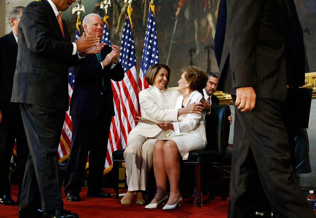 . Former U.S. first lady Nancy Reagan (R) is embraced by Speaker of the House Nancy Pelosi during a ceremony unveiling a statue of former President Ronald Reagan in the Rotunda of the U.S. Capitol June 3, 2009 in Washington, DC. The statue will become part of the National Statuary Hall Collection. Also pictured at left is former U.S. Treasury Secretary James Baker.  (Photo by Win McNamee/Getty Images)