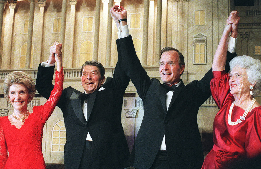 . US President Ronald Reagan (l)  raises his arms in the air with presidential hopeful George Bush (2nd-r) after President Reagan announced endorsement for Bush as the next president of the United States in Washington DC, November 5,1988. At left, First Lady Nancy Reagan, at right, Barbara Bush.  (MIKE SARGENT/AFP/Getty Images)