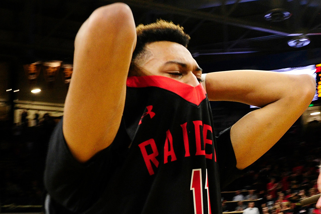 . Calvin Collins (1) of Rangeview covers his face as he walks out the arena at the Coors Events Center on March 11, 2016 in Boulder, Colorado. Eaglecrest defeated Rangeview 58-55 to advance to the 5A finals of the Colorado state high school basketball tournament.  (Photo by Brent Lewis/The Denver Post)