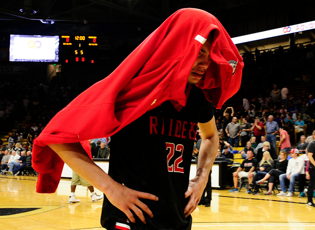 . Marquis Kraemer (22) of Rangeview covers his face as walking out of the area after losing to Eaglecrest at the Coors Events Center on March 11, 2016 in Boulder, Colorado. Eaglecrest defeated Rangeview 58-55 to advance to the 5A finals of the Colorado state high school basketball tournament.  (Photo by Brent Lewis/The Denver Post)