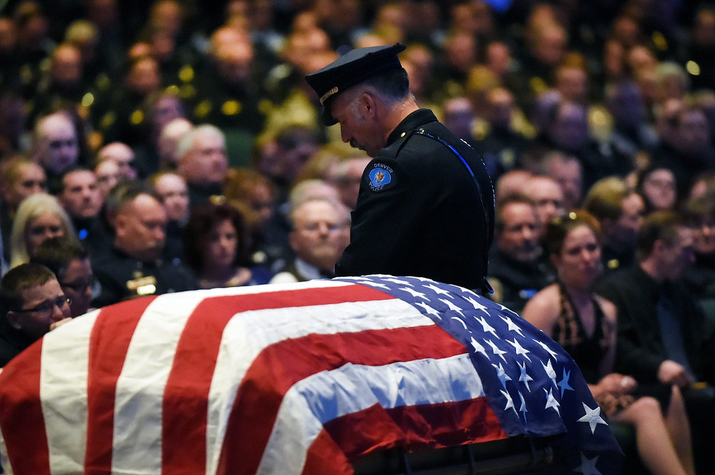 """. ARVADA, CO - MARCH 14: A Denver police officer stands watch over the flag draped casket at the memorial service for Park County Deputy Corporal Nathaniel \""""Nate\"""" Carrigan at Faith Bible Chapel on March 14, 2016 in Arvada, Colorado. Carrigan was killed in the line of duty while serving a warrant in Bailey, Colorado on February 24, 2016. (Photo by Helen H. Richardson/The Denver Post)"""