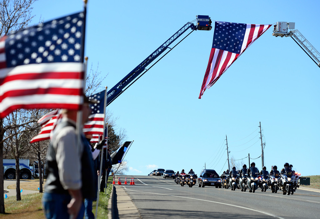 . Members of the Colorado Patriot Guard Riders line the roadway as the procession in memory of Park County Corporal Nate Carrigan heads north down Ward Rd. in Arvada on the way to Faith Bible Chapel for the memorial service. (Photo by Kathryn Scott Osler/The Denver Post)