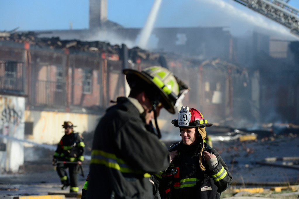 . Firefighters walk back to their trucks while extinguishing a fire at the former Rockies Inn near I-25 and Evans Avenue on April 1, 2016 in Denver, Colorado. The fire, that started in the late afternoon, destroyed the vacant motel causing a wall to fall onto an adjacent building. No injuries were reported. (Photo by Brent Lewis/The Denver Post)