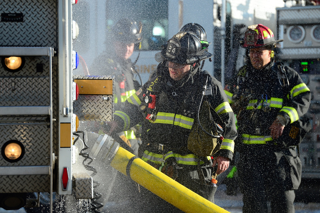 . Firefighters walk back to their engine for tools while extinguishing a fire at the former Rockies Inn near I-25 and Evans Avenue on April 1, 2016 in Denver, Colorado. The fire, that started in the late afternoon, destroyed the vacant motel causing a wall to fall onto an adjacent building. No injuries were reported. (Photo by Brent Lewis/The Denver Post)