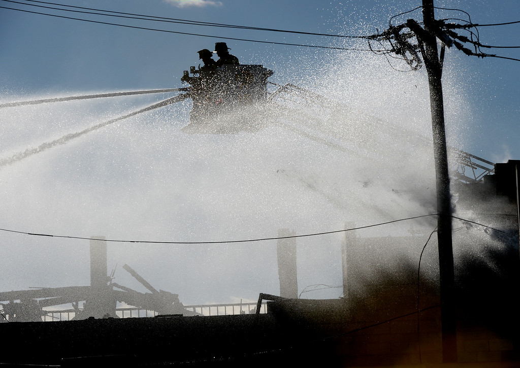 . A two alarm fire broke out at the abandoned Rockies Inn at I-25 and Evans in Denver. Denver Fire Fighters  pour water on it to put it out on Friday, April 1, 2016.  (Photo by Cyrus McCrimmon/ The Denver Post)