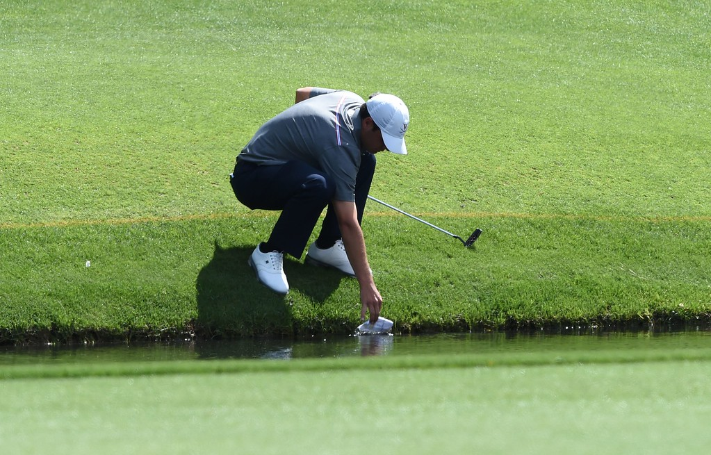 . US golfer Derek Bard fishes out his scorecard from a creek during Round 2 of the 80th Masters Golf Tournament at the Augusta National Golf Club on April 8, 2016, in Augusta, Georgia. / AFP PHOTO / DON  EMMERT/AFP/Getty Images