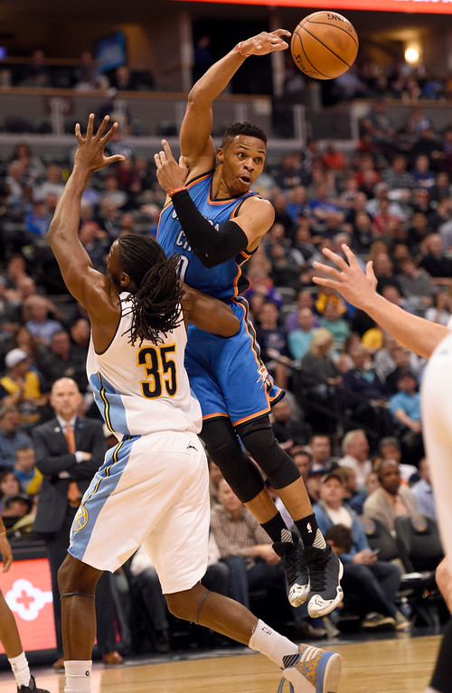 . Oklahoma City Thunder guard Russell Westbrook (0) dishes off a pass over Denver Nuggets forward Kenneth Faried (35) April 5, 2016 at Pepsi Center. (Photo By John Leyba/The Denver Post)