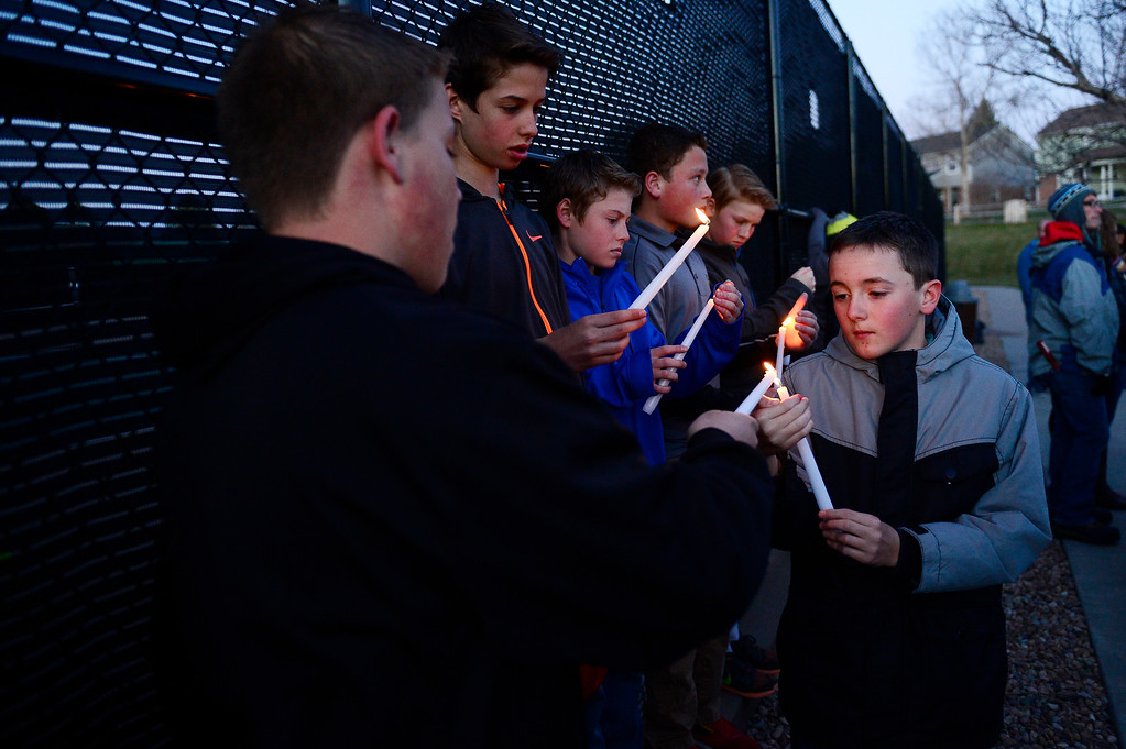 . Kade Applegate, 13 helps light his friends\' candles during a vigil for Dr. Kenneth Atkinson on April 5, 2016 in Centennial, Colorado. Close to 400 people showed up to pay their respects to Dr. Atkinson, who lost his life trying to protect a woman whose husband shot her. (Photo by Brent Lewis/The Denver Post)
