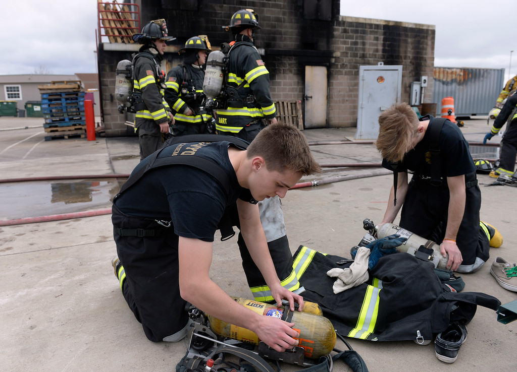 . Tyler Amfahr, 18, and Jordan Friel, 17, prepare their gear for their training. Douglas County School District students enrolled in the Fire Science program join firefighters in search and rescue and extinguishment scenarios at the South Metro Fire Rescue Training Center in Parker. The students have been training all year with the firefighters who have all volunteered their time to help train the students through this program. (Photo by Kathryn Scott Osler/The Denver Post)