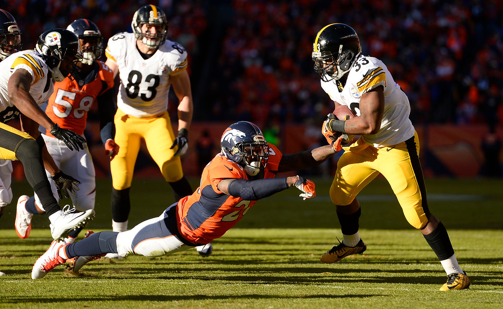 . Pittsburgh Steelers running back Fitzgerald Toussaint (33) sings away from Denver Broncos free safety Darian Stewart (26) as he picks up a few yards during the first quarter January 17, 2016 in the Divisional Round Playoff game at Sports Authority Field at Mile High Stadium. (Photo By Helen Richardson/The Denver Post)