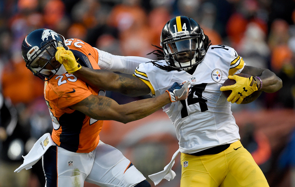 . Pittsburgh Steelers wide receiver Sammie Coates (14) stiff arms Denver Broncos cornerback Chris Harris (25) after a gain during the third quarter January 17, 2016 in the Divisional Round Playoff game at Sports Authority Field at Mile High Stadium. (Photo By Helen Richardson/The Denver Post)