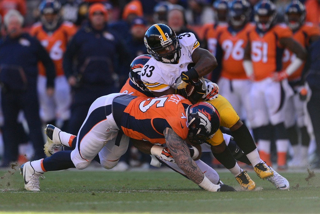 . Pittsburgh Steelers running back Fitzgerald Toussaint (33) gets hit by Denver Broncos defensive end Derek Wolfe (95) after short gain in the first January 17, 2016 in the Divisional Round Playoff game at Sports Authority Field at Mile High Stadium. (Photo By Eric Lutzens/The Denver Post)