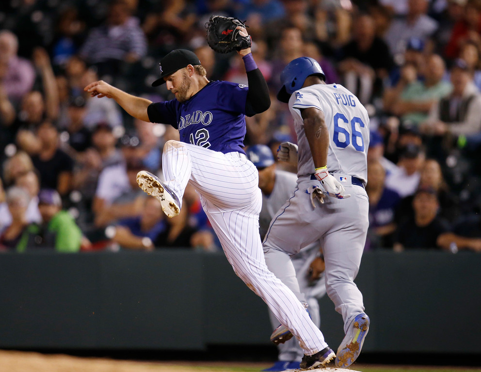 . Colorado Rockies first baseman Mark Reynolds, front, pulls in a high throw to put out Los Angeles Dodgers\' Yasiel Puig at first base in the eighth inning of a baseball game Friday, April 22, 2016, in Denver. Colorado won 7-5. (AP Photo/David Zalubowski)