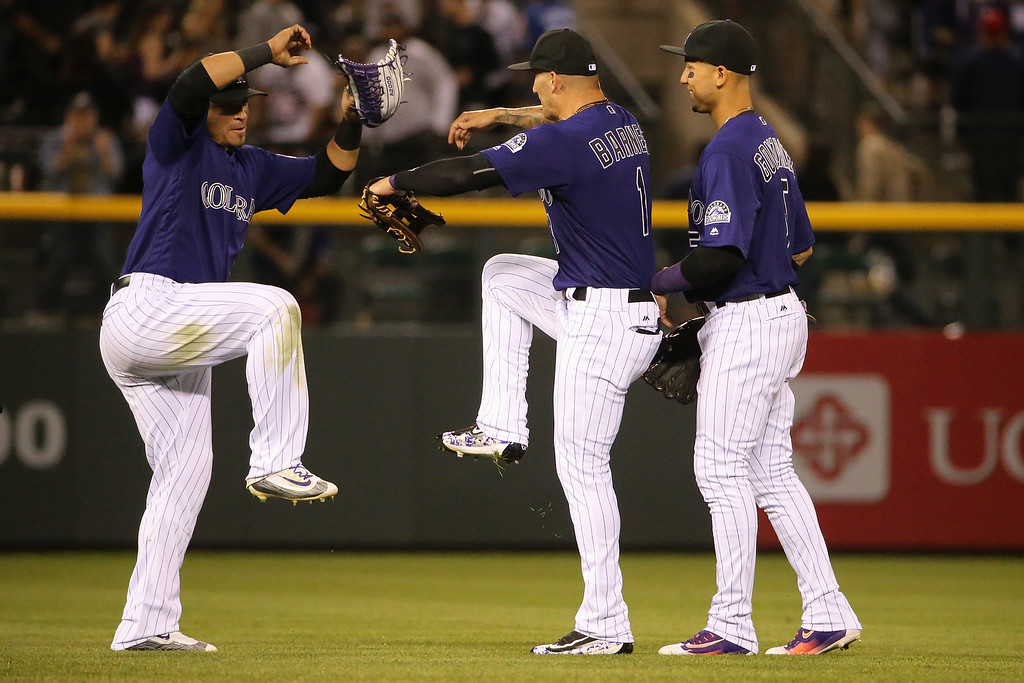 . DENVER, CO - APRIL 22:  Gerardo Parra #8, Brandon Barnes #1 and Carlos Gonzalez #5 of the Colorado Rockies celebrate their victory over the Los Angeles Dodgers at Coors Field on April 22, 2016 in Denver, Colorado. The Rockies defeated the Dodgers 7-5.  (Photo by Doug Pensinger/Getty Images)