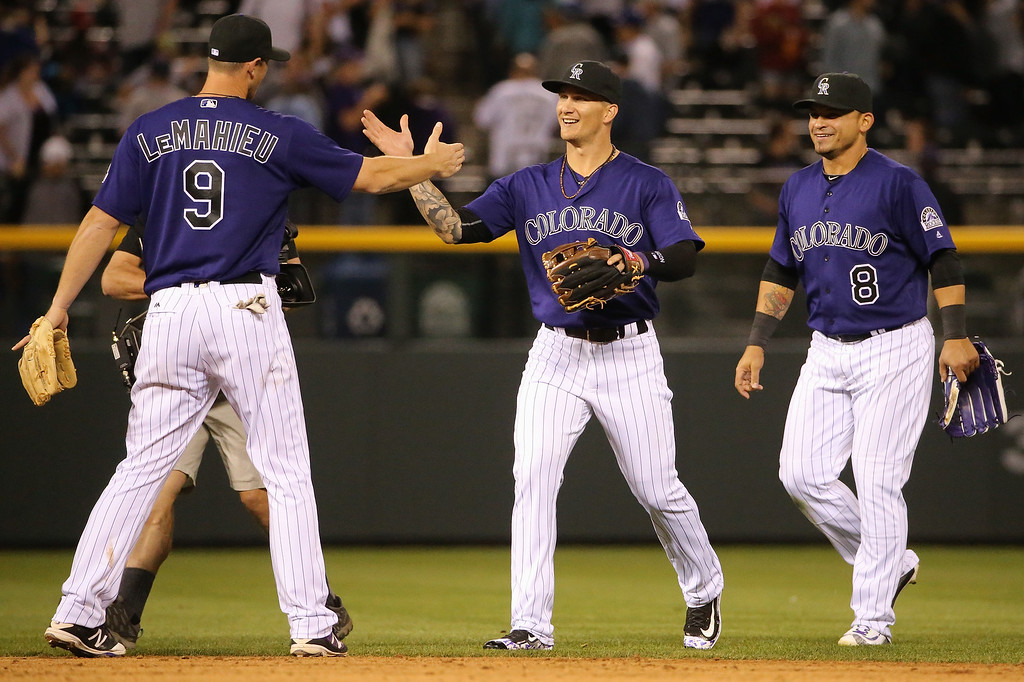 . DENVER, CO - APRIL 22:  DJ LeMahieu #9, Brandon Barnes #1 and Gerardo Parra #8 of the Colorado Rockies celebrate their victory over the Los Angeles Dodgers at Coors Field on April 22, 2016 in Denver, Colorado. The Rockies defeated the Dodgers 7-5. (Photo by Doug Pensinger/Getty Images)