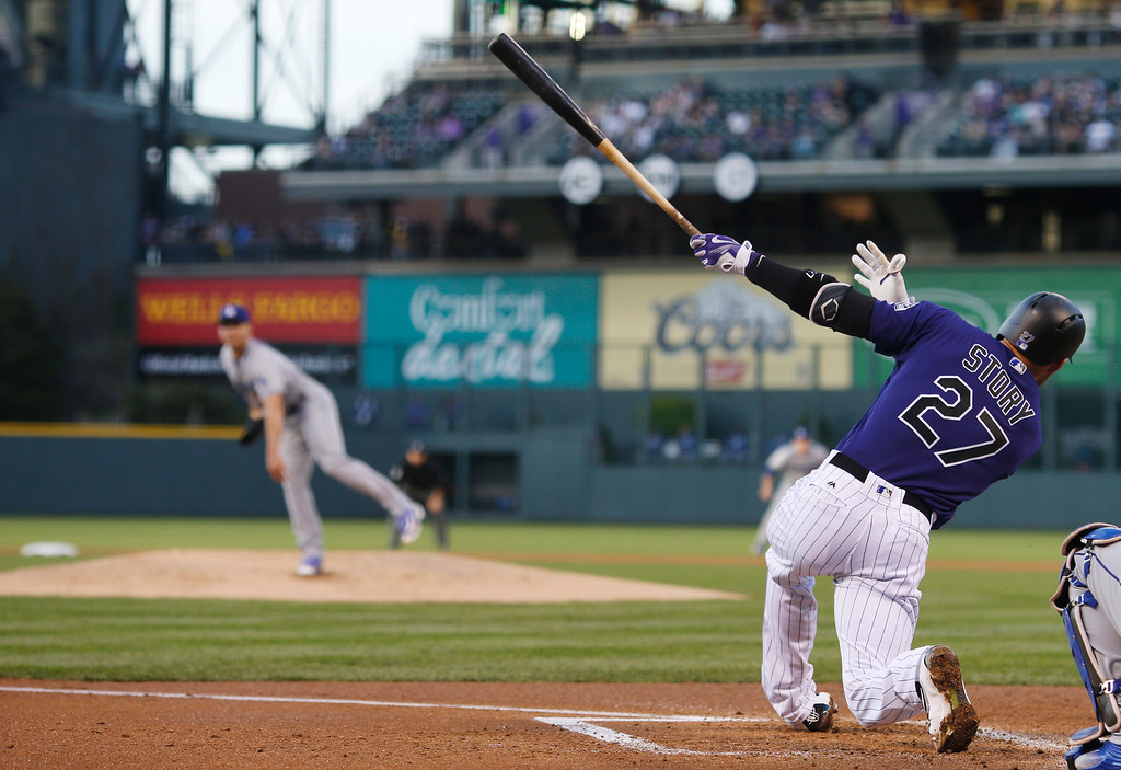 . Colorado Rockies\' Trevor Story (27) swings at a pitch from Los Angeles Dodgers starting pitcher Scott Kazmir, left, in the first inning of a baseball game Friday, April 22, 2016, in Denver. (AP Photo/David Zalubowski)