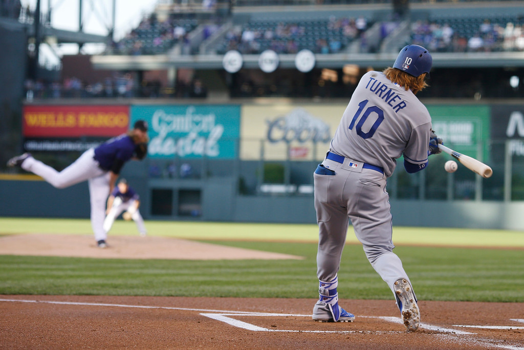 . Los Angeles Dodgers\' Justin Turner, front, swings for but misses a pitch from Colorado Rockies starter Jon Gray in the first inning of a baseball game Friday, April 22, 2016, in Denver. (AP Photo/David Zalubowski)