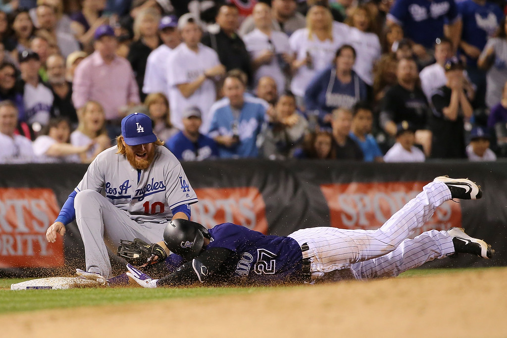 . DENVER, CO - APRIL 22:  Third baseman Justin Turner #10 of the Los Angeles Dodgers tags out Trevor Story #27 of the Colorado Rockies as he attempts to triple in the fifth inning at Coors Field on April 22, 2016 in Denver, Colorado.  (Photo by Doug Pensinger/Getty Images)