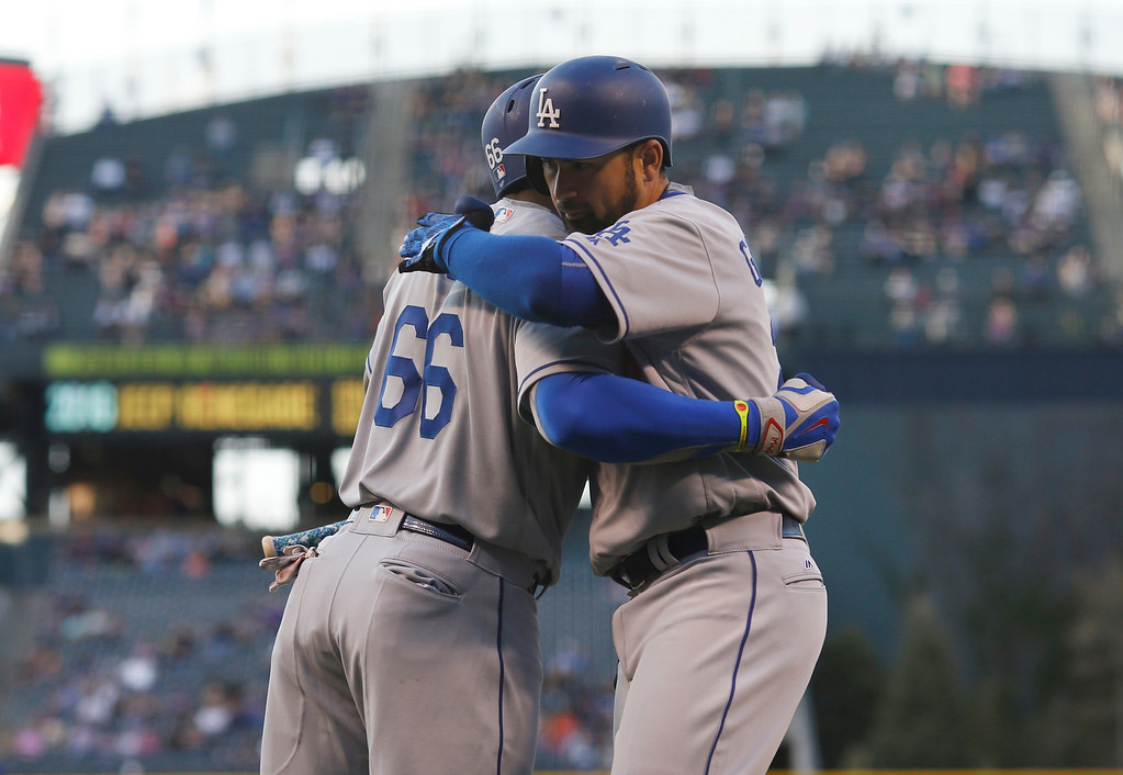 . Los Angeles Dodgers\' Adrian Gonzalez, right, is congratulated by teammate Yasiel Puig after hitting a solo home run off Colorado Rockies starting pitcher Jon Gray in the first inning of a baseball game Friday, April 22, 2016, in Denver. (AP Photo/David Zalubowski)