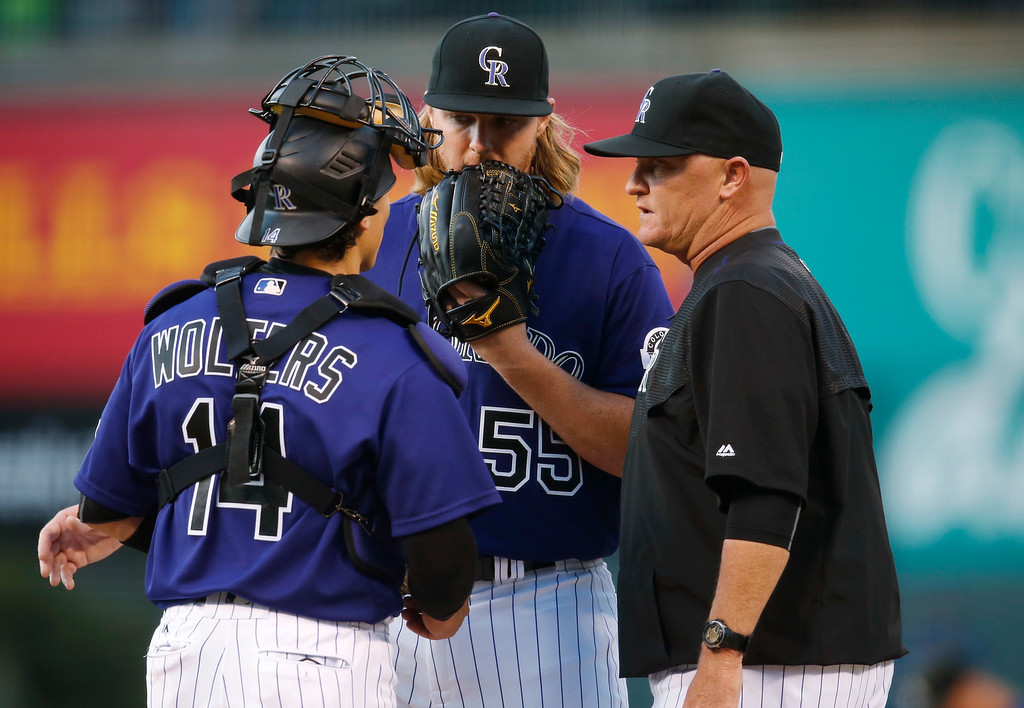 . Colorado Rockies pitching coach Steve Foster, right, confers with catcher Tony Wolters, left, and starting pitcher Jon Gray after Gray gave up a solo home run to Los Angeles Dodgers\' Adrian Gonzalez in the first inning of a baseball game Friday, April 22, 2016, in Denver. (AP Photo/David Zalubowski)