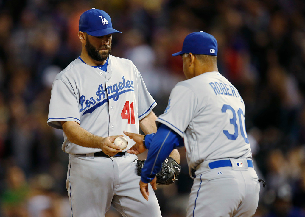 . Los Angeles Dodgers relief pitcher Chris Hatcher, left, hands over the ball to manager Dave Roberts after giving up a two-run triple to Colorado Rockies\' Brandon Barnes during the eighth inning of a baseball game Friday, April 22, 2016, in Denver. Colorado won 7-5. (AP Photo/David Zalubowski)
