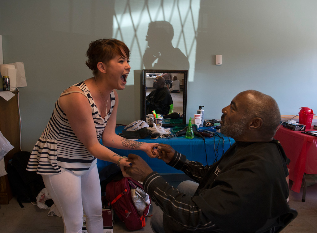 """. DENVER, CO - APRIL 25: Liz Lambert, left, not only give Air Force veteran Bobby Hendrix a haircut, but celebrates helping him finding furniture and other items for his new apartment. Lambert and other stylists all donated their time to give the haircuts. Volunteers of America along with other organizations, hosts a \""""Haircuts for Veterans\"""" event at the Bill Daniels Veteran Service Center in Denver on Monday, April 25, 2016. Along with the haircuts, veterans have access to housing service assistance, assistance with job and education opportunities, as well as a hot meal.  (Photo by Kathryn Scott Osler/The Denver Post)"""